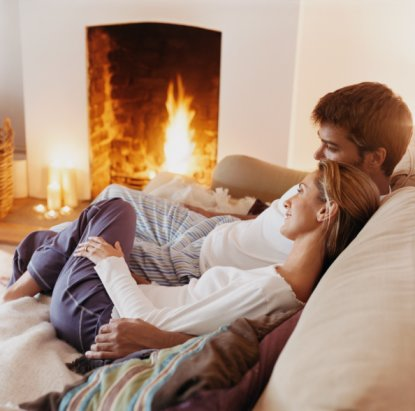 Couple Sitting Close to Each Other on a Sofa by a Fireplace